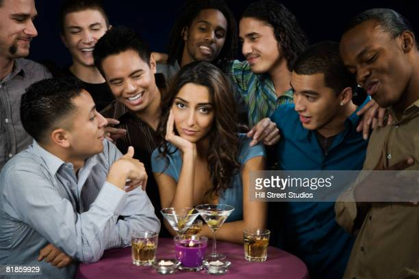 Multi-ethnic men talking to bored woman
