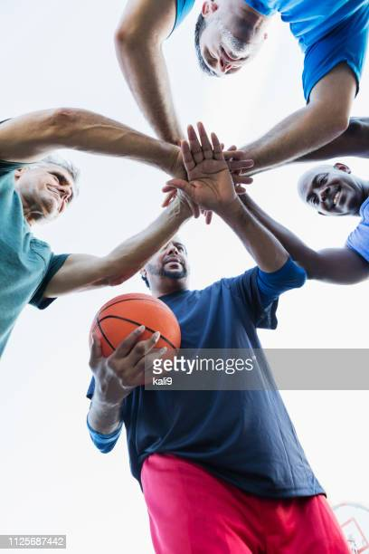 multi-ethnic men with basketball, in huddle - basketball team stock pictures, royalty-free photos & images