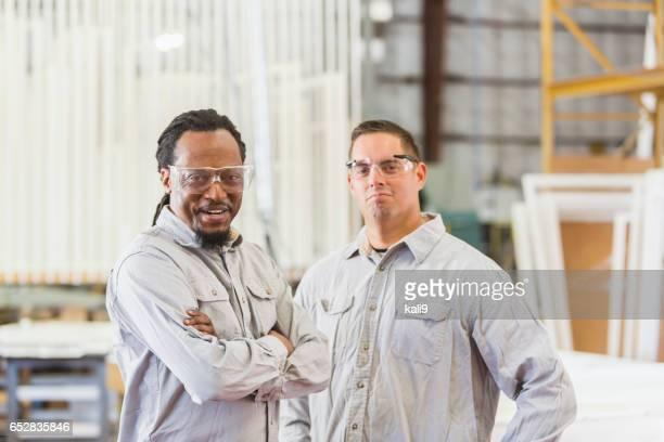 Multi-ethnic men working in shutter factory