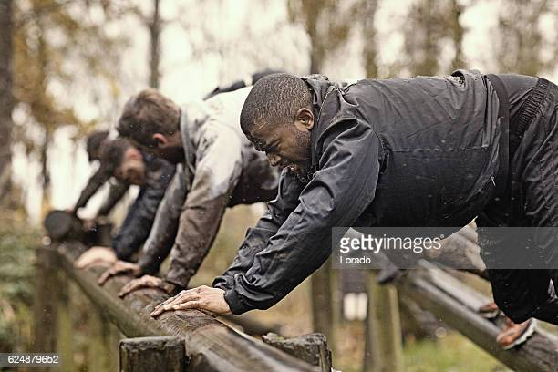 Multiethnic mud run team of men climbing along obstacle course