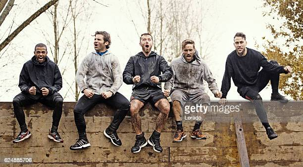 Multiethnic mud run team of men sitting on obstacle course