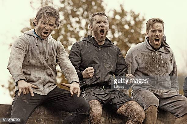 Multiethnic mud run team of men sitting shouting obstacle course
