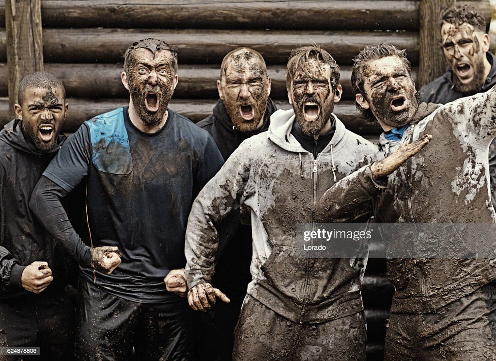 Multiethnic mud run team of men yelling during obstacle course : Stock Photo