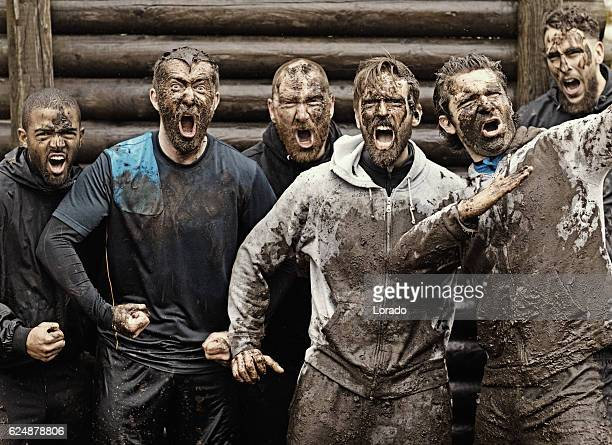 multiethnic mud run team of men yelling during obstacle course - tag stock-fotos und bilder