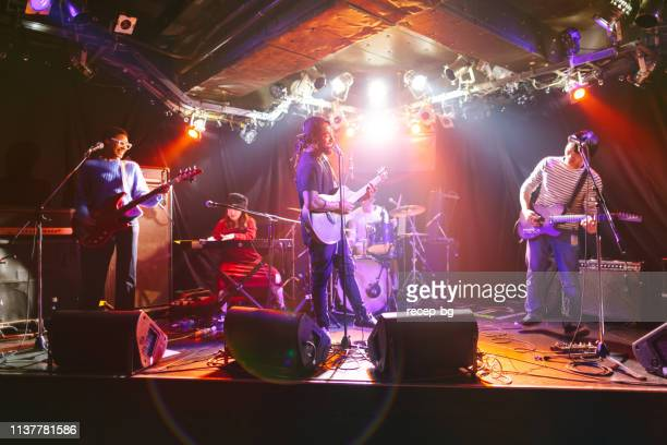 multi-ethnic music performance group performing on stage - five people stock pictures, royalty-free photos & images