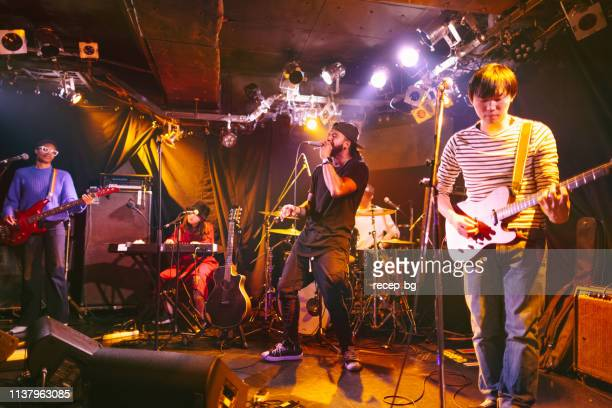 multi-ethnic music performance group performing on stage - rock band stock pictures, royalty-free photos & images