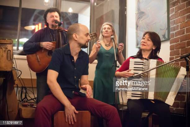 multi-ethnic musicians singing, playing guitar, accordian, peruvian cajon in cafe - accordionist stock pictures, royalty-free photos & images