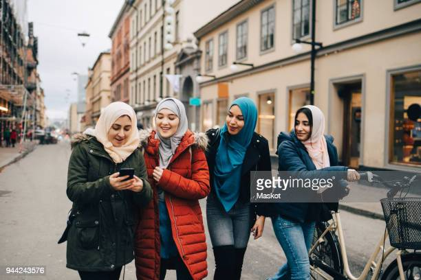 multi-ethnic muslim friends walking with bicycle and mobile phone on street in city - traditional clothing stock pictures, royalty-free photos & images