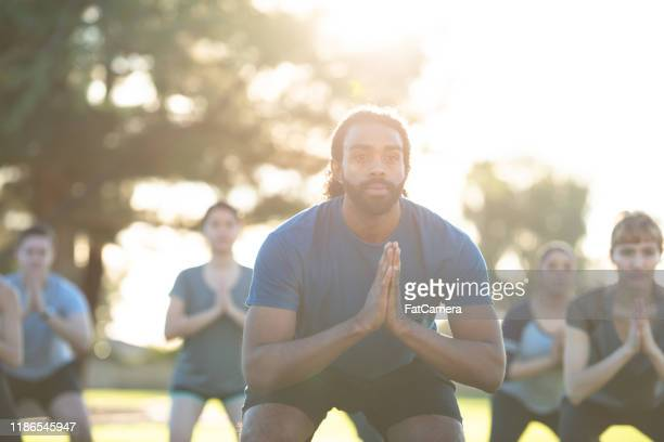 multi-ethnic outdoor yoga fitness class stock photo - slim stock pictures, royalty-free photos & images