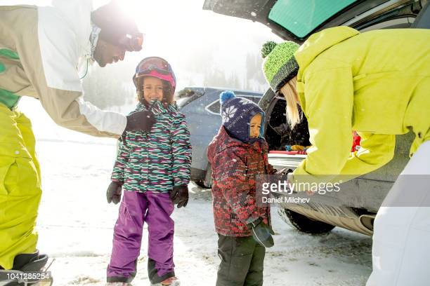 multi-ethnic parents putting jackets, hats and gloves on their kids at a ski resort on a snowy day. - ski wear stock pictures, royalty-free photos & images