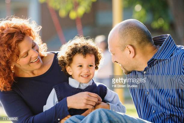 Multi-ethnic parents smiling at son