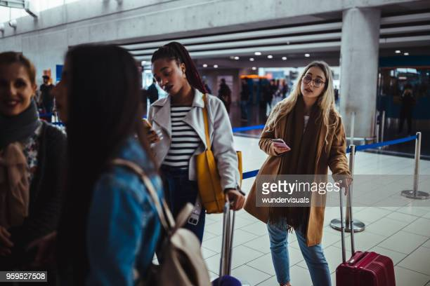 multi-ethnic passengers standing in queue for check-in at airport - lining up stock pictures, royalty-free photos & images