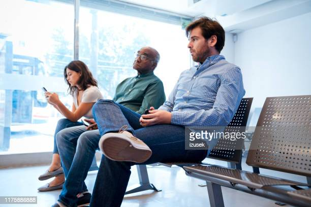 multi-ethnic patients sitting at waiting room - outpatient care stock pictures, royalty-free photos & images