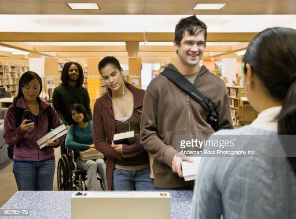 multi-ethnic people checking out library books - book store stock photos and pictures