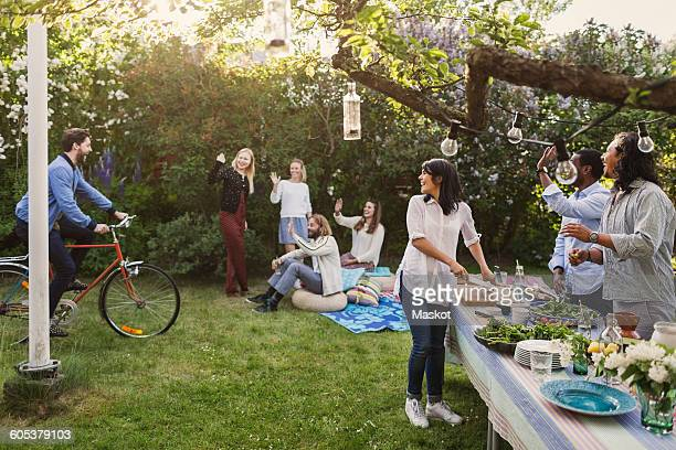 Multi-ethnic people greeting friend riding bicycle in yard during summer party