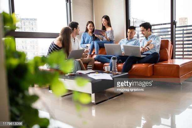 personnes multiethniques s'amusant tout en travaillant à la maison - groupe moyen de personnes photos et images de collection