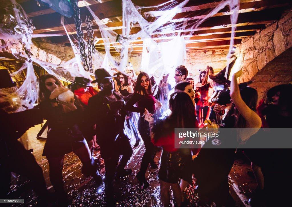 Multi-ethnic people in Halloween costumes having fun at dungeon nightclub : Stock Photo