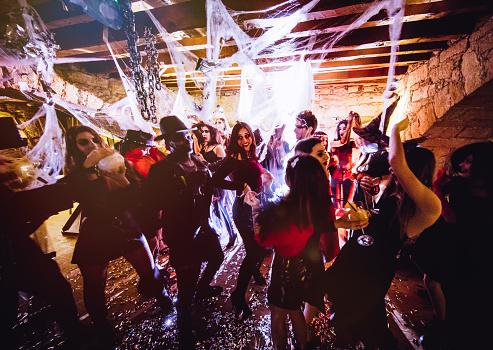 Multi-ethnic people in Halloween costumes having fun at dungeon nightclub 915628830