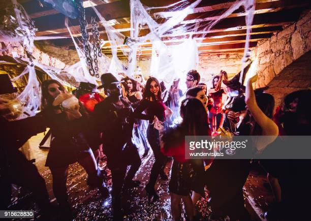 multi-ethnic people in halloween costumes having fun at dungeon nightclub - halloween party stock photos and pictures