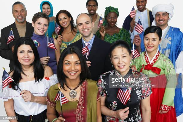 Multi-ethnic people in traditional dress holding American flags