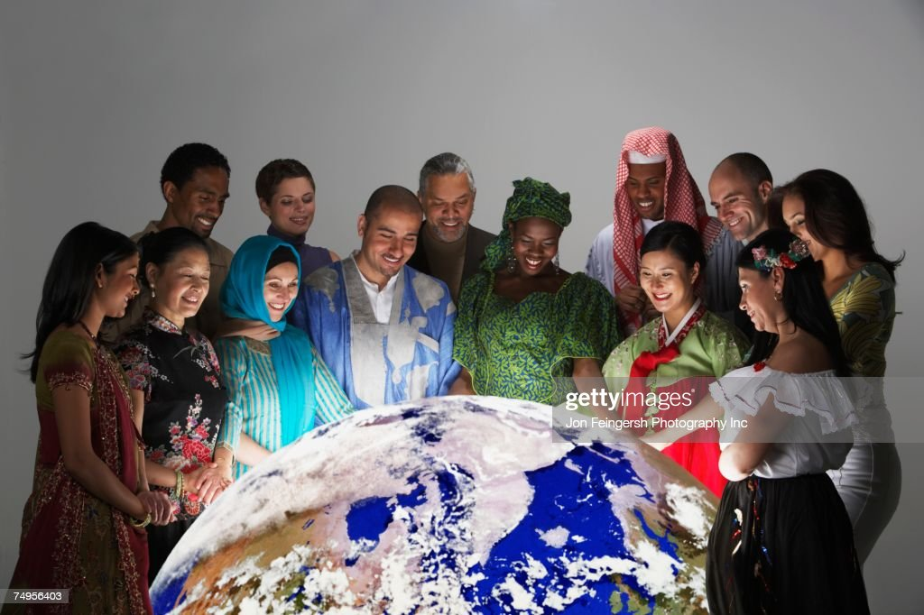 Multi-ethnic people in traditional dress looking at globe : Stock Photo