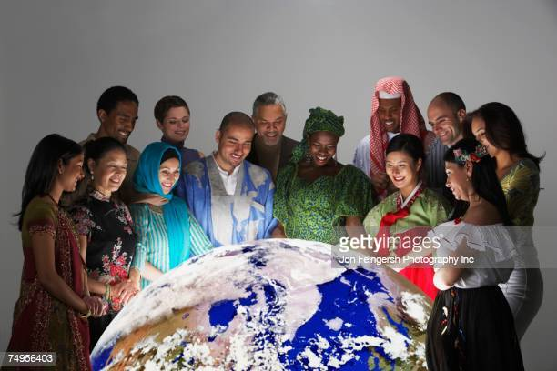 multi-ethnic people in traditional dress looking at globe - culturen stockfoto's en -beelden