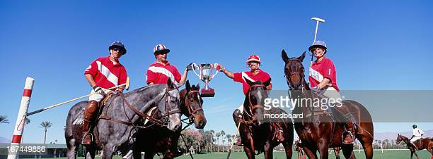 multiethnic polo team celebrating with trophy on field - indio california stock pictures, royalty-free photos & images