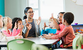Multi-ethnic preschool teacher and students in classroom