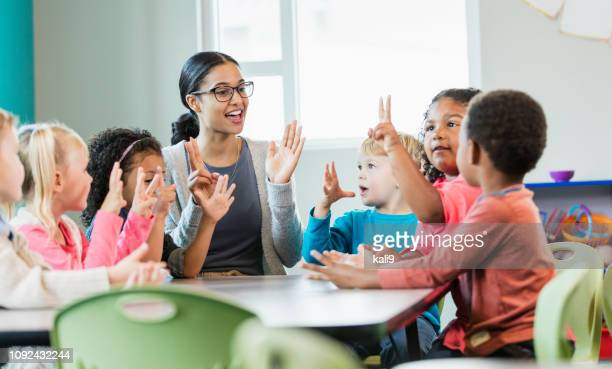 multi-ethnic preschool teacher and students in classroom - preschool stock pictures, royalty-free photos & images