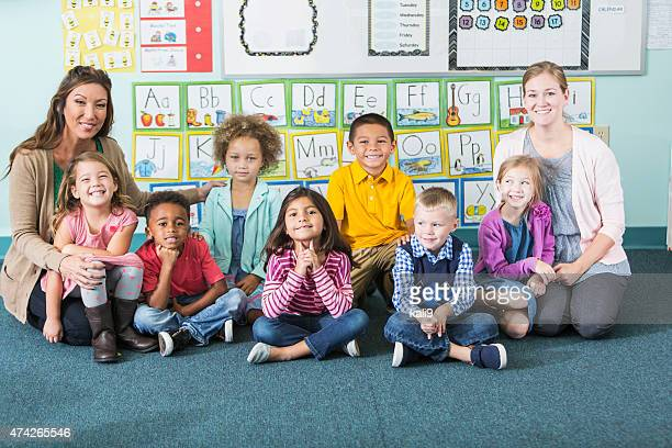 multi-ethnic preschoolers and teachers in classroom - assistant stock pictures, royalty-free photos & images