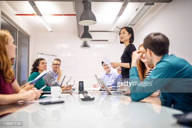 multi-ethnic professionals discussing in meeting - promotion employment stock pictures, royalty-free photos & images