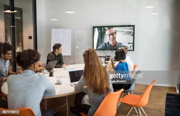 Multi-ethnic professionals video conferencing in meeting room
