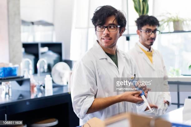 Profesor multiétnica y estudiante de laboratorio de Ciencias de la Universidad.
