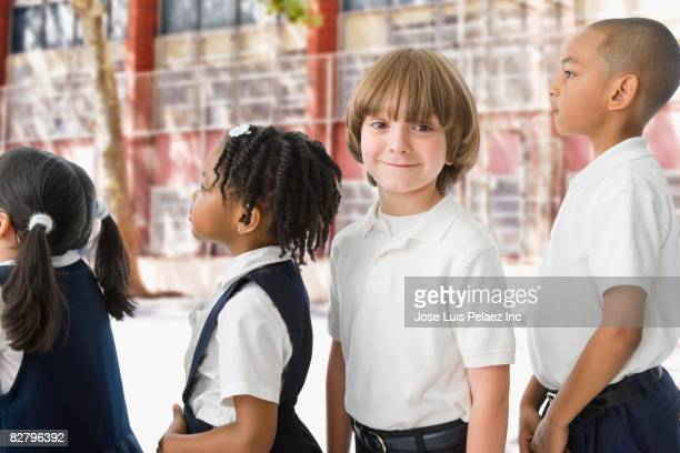 multi-ethnic school children in uniforms in a row outdoors - schuluniform stock-fotos und bilder