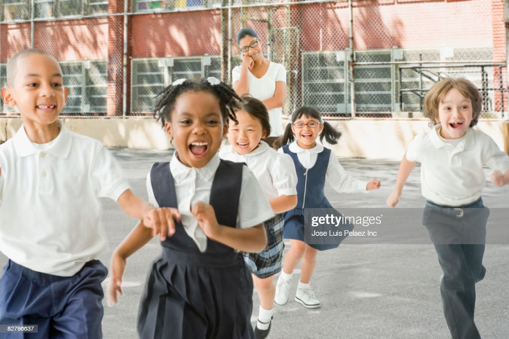 Multi-ethnic school children running from teacher outdoors : Stock Photo