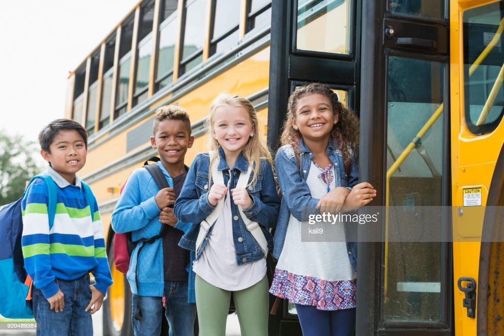 Multi-ethnic school children standing outside bus : Stock Photo