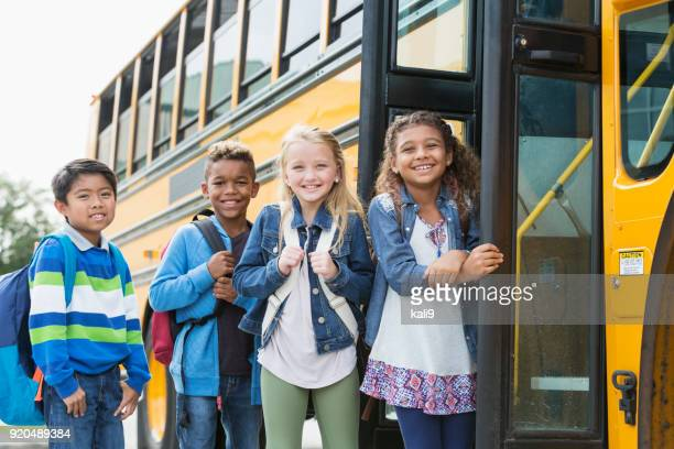 multi-ethnic school children standing outside bus - boarding stock pictures, royalty-free photos & images
