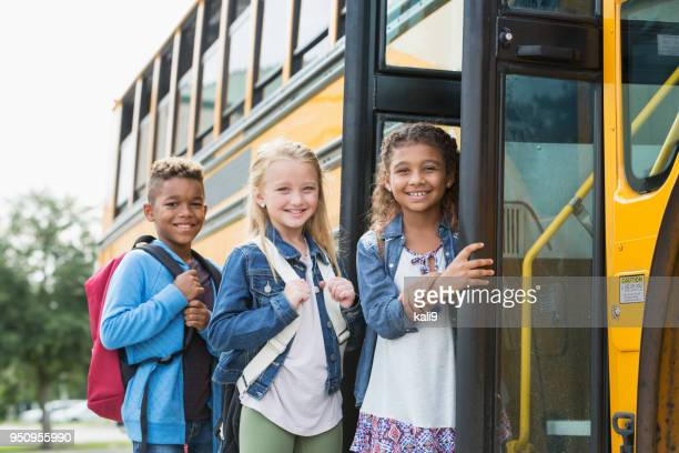 multi-ethnic school children standing outside bus - open backpack stock pictures, royalty-free photos & images
