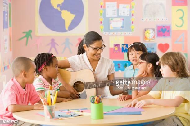 Multi-ethnic school children watching teacher play guitar