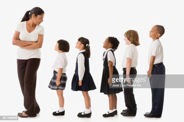 Multi-ethnic school teacher and children in uniforms in a row