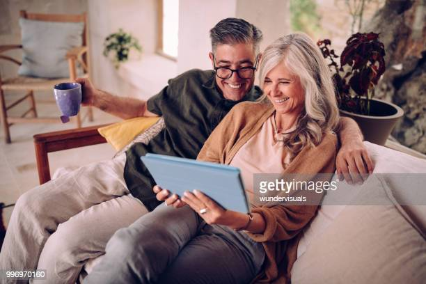 multi-ethnic senior couple making online video call using digital tablet - senior couple stock pictures, royalty-free photos & images