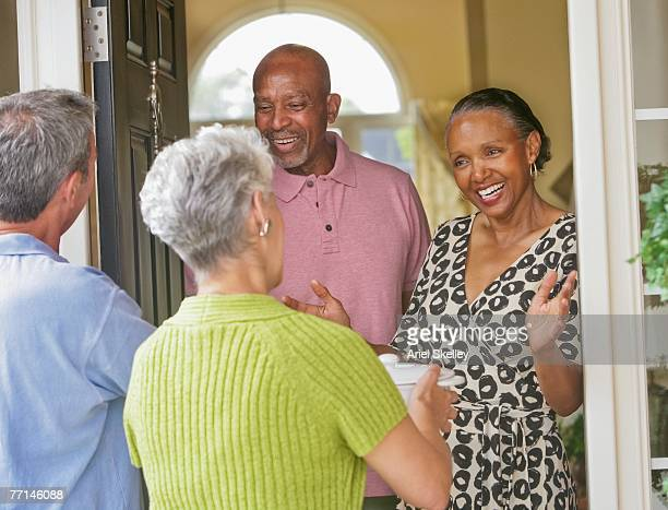 Multi-ethnic senior couples greeting in doorway