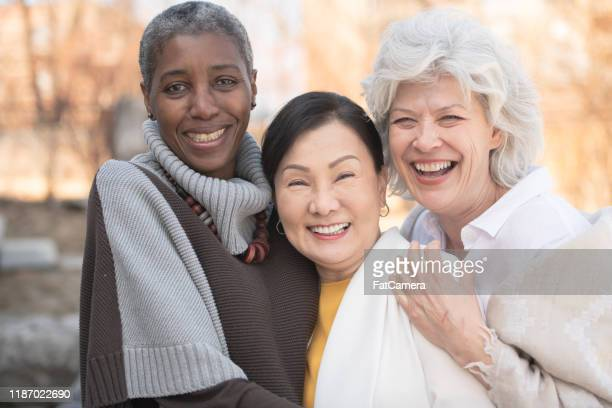 multi-ethnic senior girlfriends outside stock photo - medicare stock pictures, royalty-free photos & images