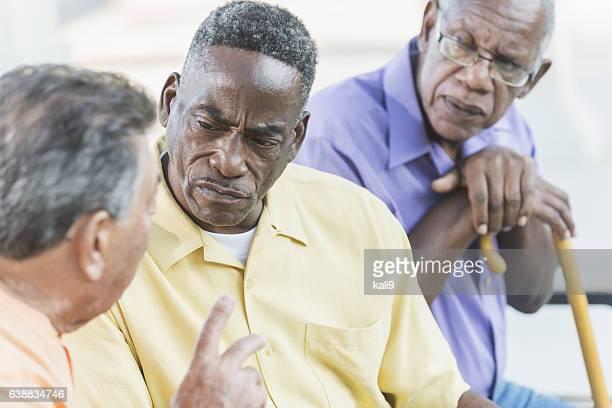 Multi-ethnic senior men on park bench, talking