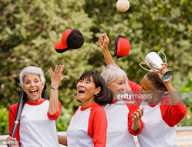 multi-ethnic senior women in baseball uniforms cheering - softball sport stock pictures, royalty-free photos & images