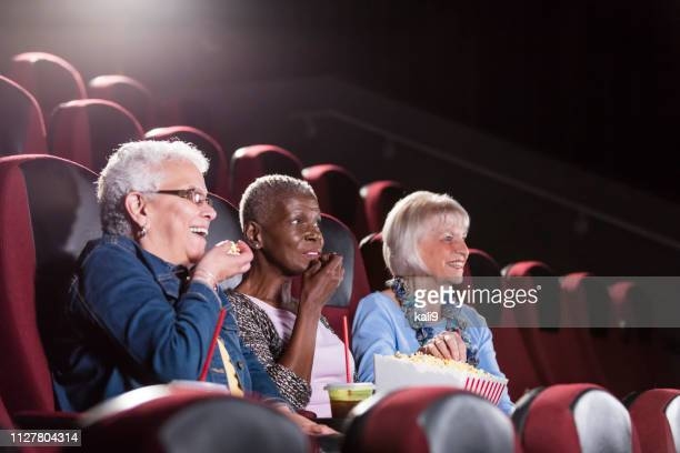 multi-ethnic senior women in movie theater watching film - girlfriends films stock pictures, royalty-free photos & images