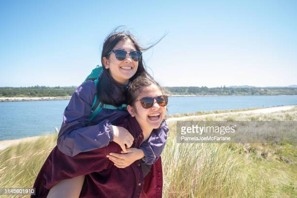 multi-ethnic siblings, younger sister piggybacking older on oregon sand dunes - oregon coast stock pictures, royalty-free photos & images