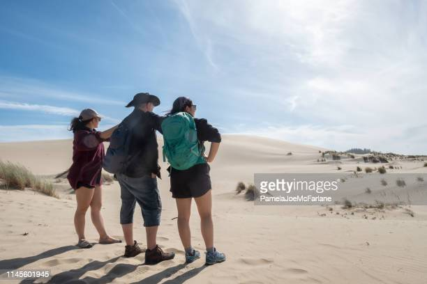 multi-ethnic sisters and father gaze at oregon sand dune landscape - national recreation area stock pictures, royalty-free photos & images