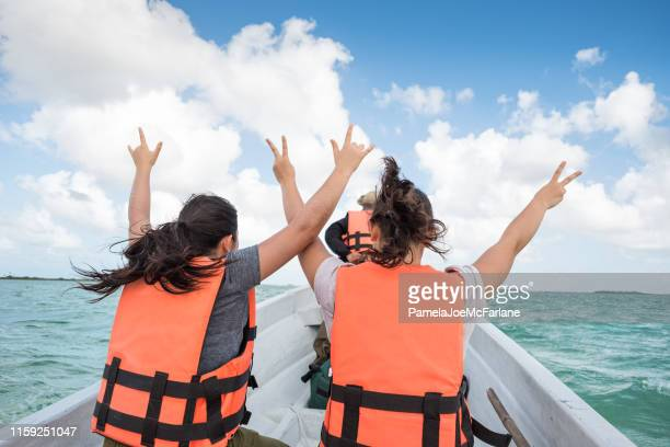 multi-ethnic sisters on boat tour raising arms in wind, mexico - life jacket stock pictures, royalty-free photos & images