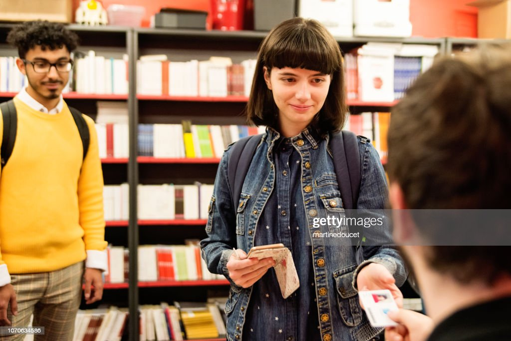 Multi-ethnic students buying books in student association classroom. : Stock Photo